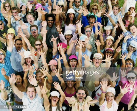 Crowd of young adults yelling, raising hands in air, portrait : Stock Photo