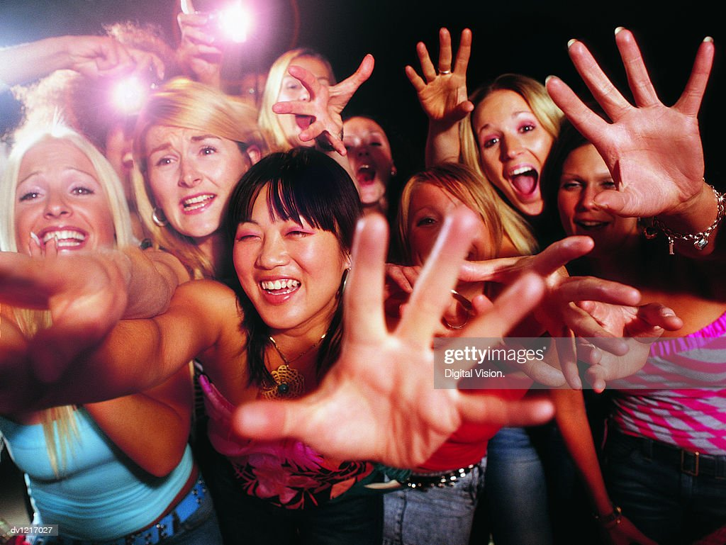 Crowd of Young, Female Fans Stretching Out Their Hands and Shouting : Stock Photo