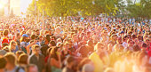 Large crowd of young people crowding city streets in a sunny day during a music festival, walking, dancing and having fun. Street parties are a common way for teenagers to entertain together during th
