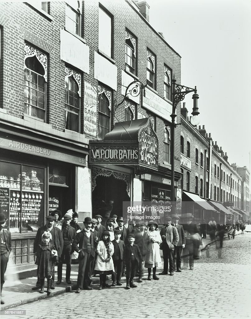 Crowd outside the Russian Vapour Baths, Brick Lane, Stepney, London, 1904. People stand in the street by the entrance to the baths; the porch and windows above are influenced by the Russian 'onion dome' style. A Rosenberg's jeweller's shop is presumably run by a Jewish immigrant of which there were many in the East End at this time.