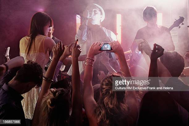Crowd photographing band in club