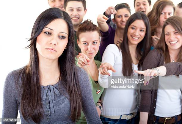 Crowd pointing fingers at a young woman