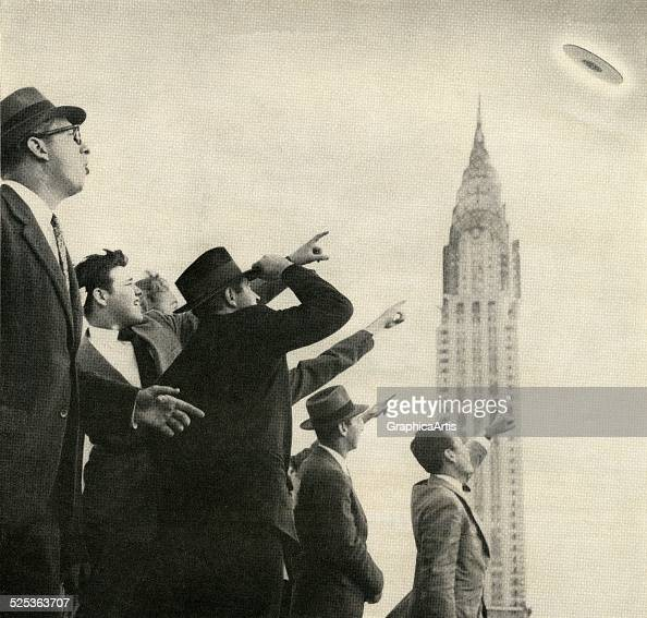 A crowd points to a UFO flying over the Chrysler Building in Manhattan photograph 1951