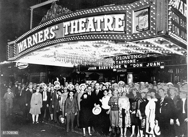 A crowd poses under the kiosk of Warners' Theatre at 1579 Broadway New York New York August 1926 The kisok advertises both Alan Crosland's 1926 film...