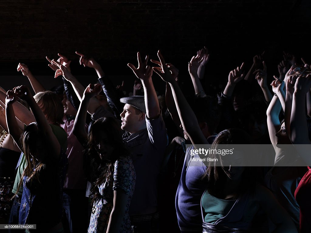 Crowd raising arms at party in night club : Stock Photo