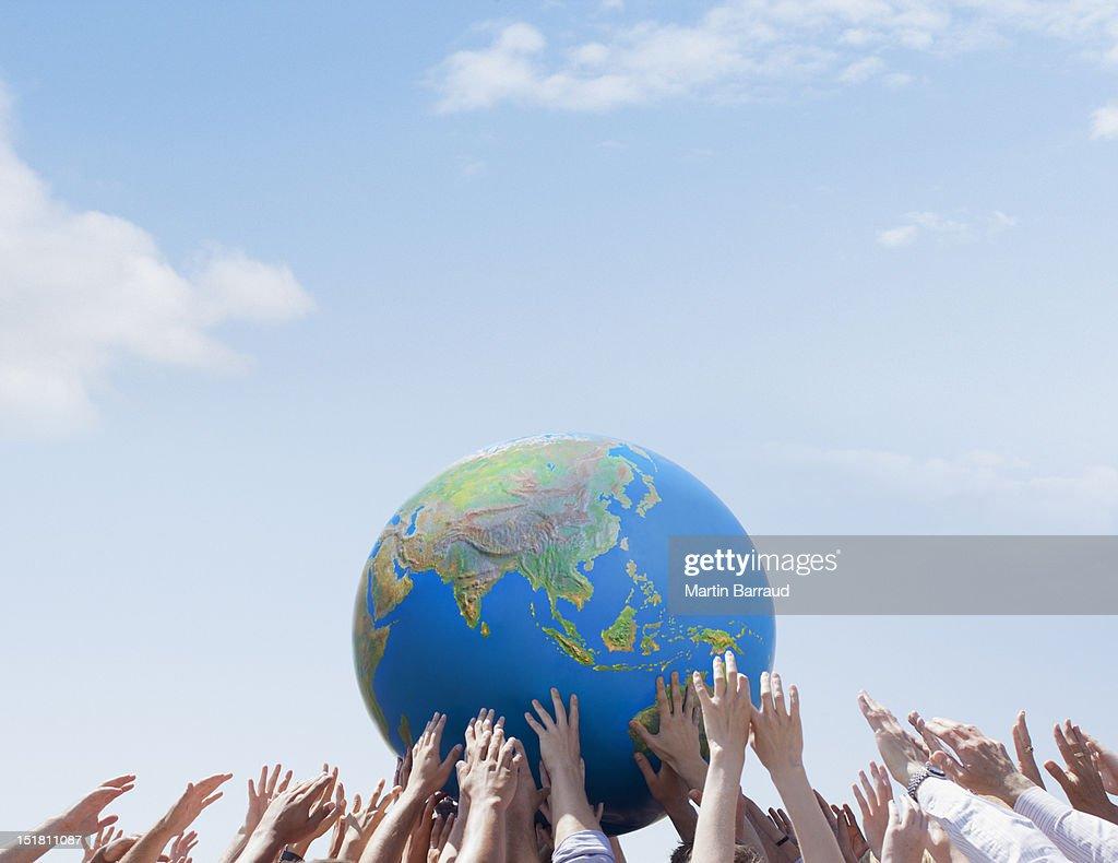 Crowd reaching for globe : Stock Photo