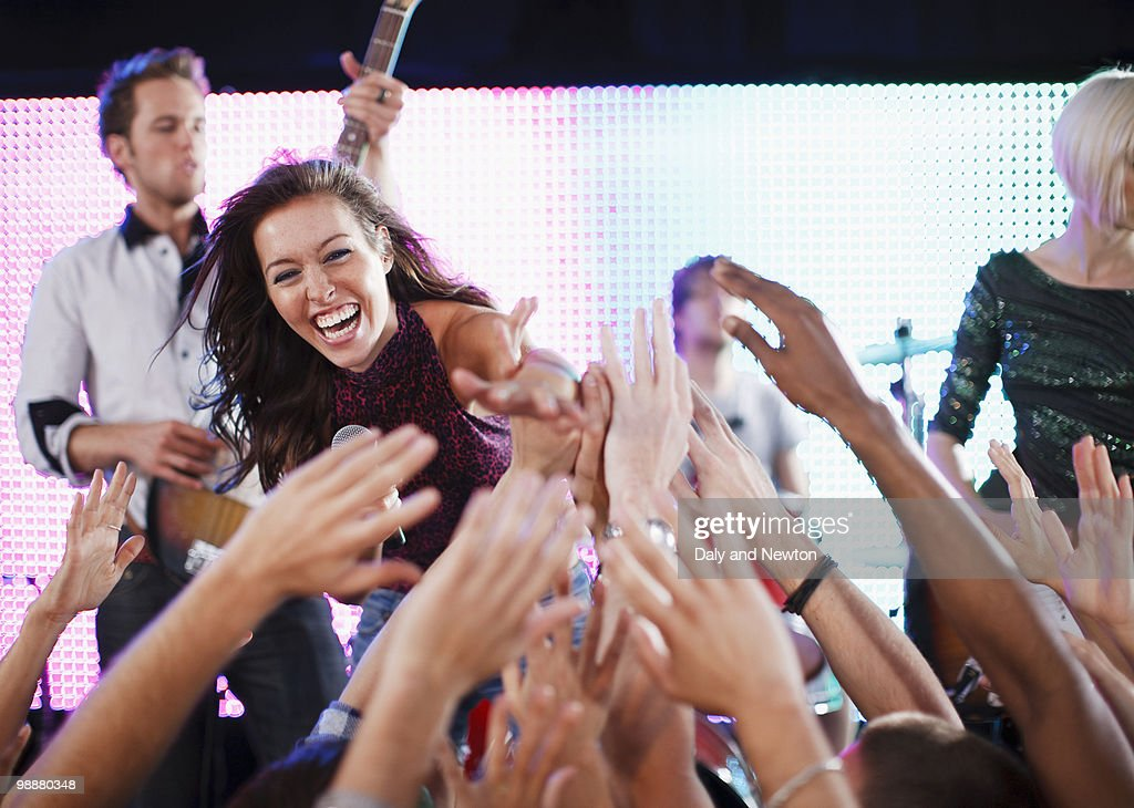 Crowd reaching toward female singer on stage : Stock Photo