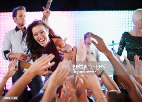 Crowd reaching toward female singer on stage : Foto de stock