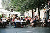 This long shot shows many diverse people sitting in an outdoor dinning area near a restaurant in Palma, Majorca.  The tables are covered by tall, white, fabric, sun-shade umbrellas on the left and mat