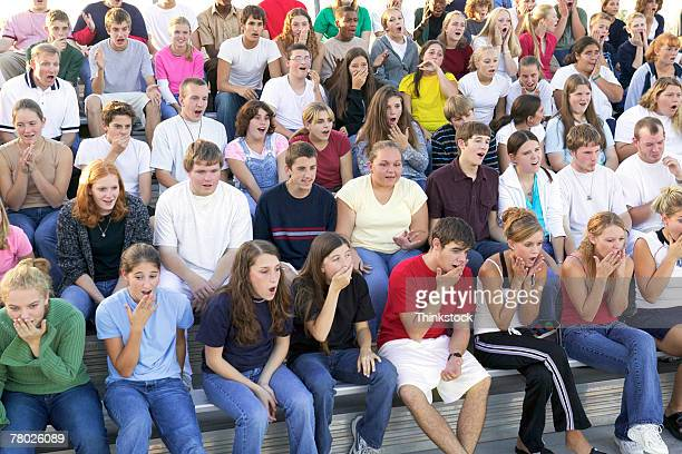 A crowd sits in the stands with looks of surprise and shock at what is happening