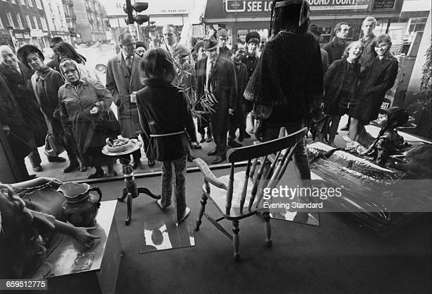 A crowd viewing the window display at the Apple boutique run by the Beatles' Apple Corps on the corner of Baker Street and Paddington Street London...