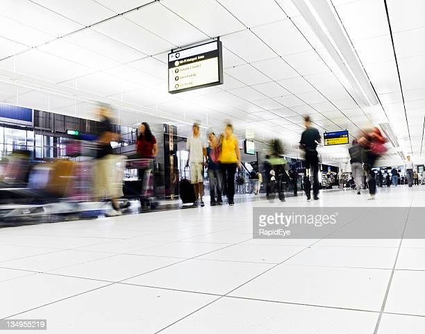 Crowd walks towards camera in an airport concourse