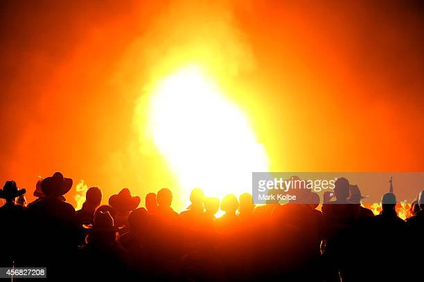 A crowd watch on as a flammable canister explodes in a large fire burning in the 'Ute Paddock' camp ground on the second day of the 2014 Deni Ute...