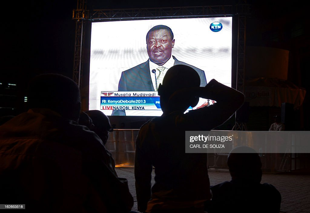 A crowd watch Presidential candidate Musalia Mudavadi on a large screen in Central Nairobi broadcasting the last televised debate for the 2013 Kenya elections on February 25, 2013. Kenyans will vote for a new leader on March 4, 2013. AFP PHOTO/Carl de Souza