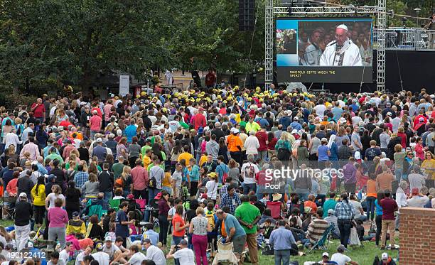 A crowd watches Pope Francis speak on a jumbotron from the Cathedral Basilica of Saints Peter and Paul on Independence Mall September 26 2015 in...