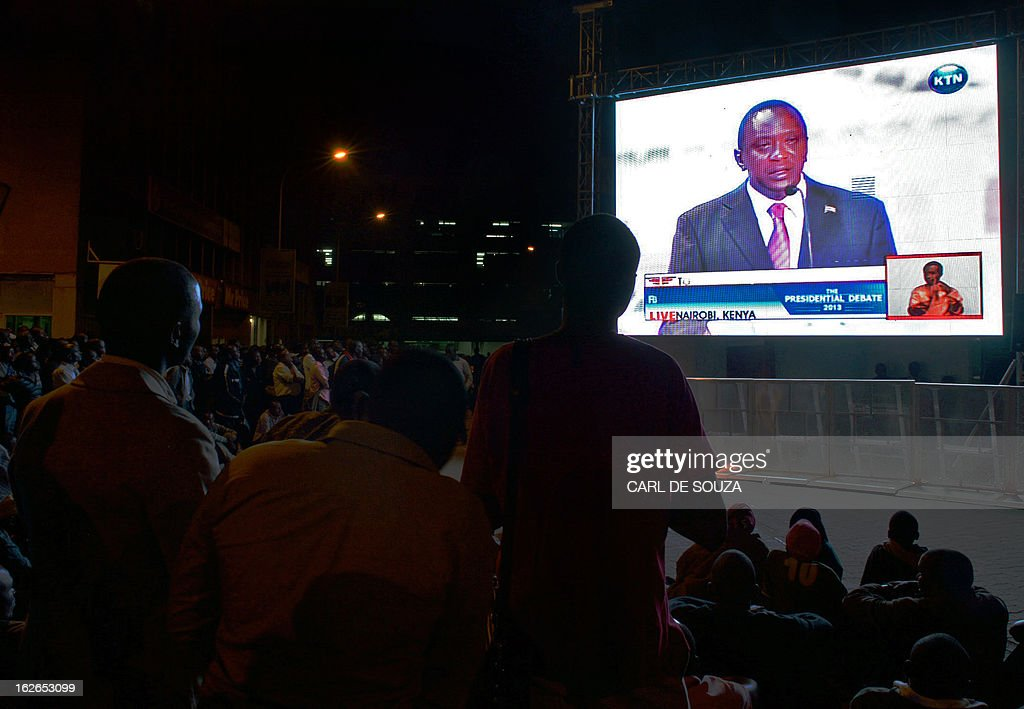 A crowd watches Presidential candidate Uhuru Kenyatta during the second and last televised debate for the 2013 Kenya elections on a large screen in Central Nairobi on February 25, 2013. Kenyans will vote for a new leader on March 4, 2013. AFP PHOTO/Carl de Souza