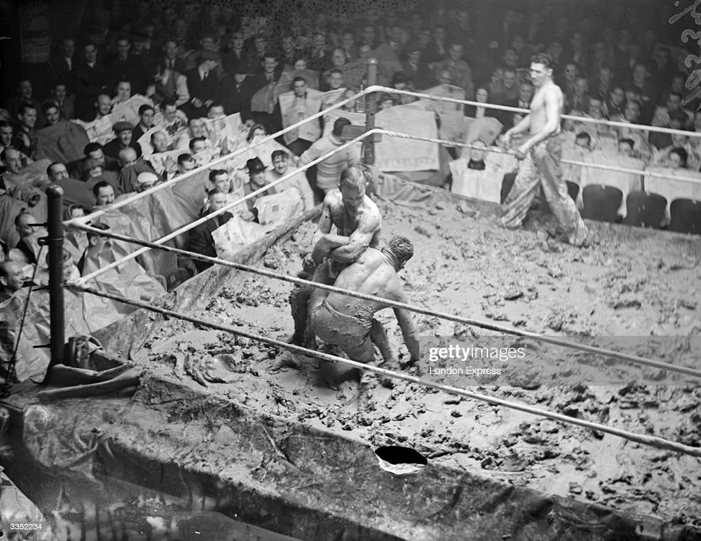 A crowd watching a mud wrestling match in a ring.