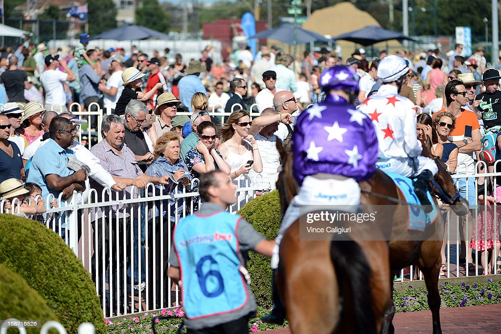 Crowd watching horses parading in the mounting yard during Caulfield races at Caulfield Racecourse on December 26, 2012 in Melbourne, Australia.