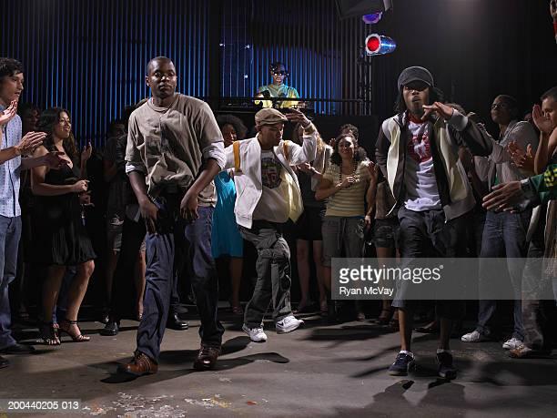 Crowd watching three men breakdance in club, DJ in background