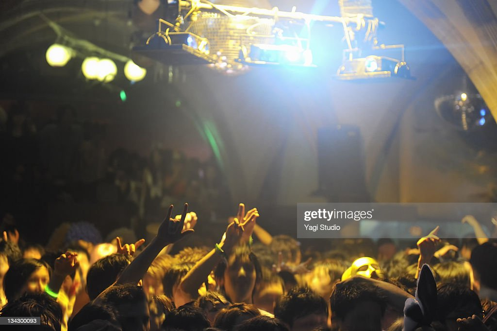 Crowd with arms in air at nightclub music. : Stock Photo
