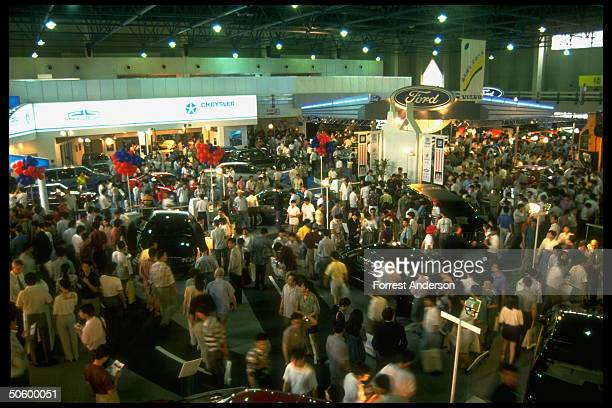 Crowded auto show floor featuring for auto makers topofline cars