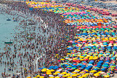 crowded beach with umbrellas and people in the water