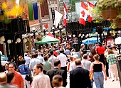 Crowded downtown sidewalk in the summer.