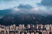 Crowded Residential Highrises Building Under Hill and Cloud