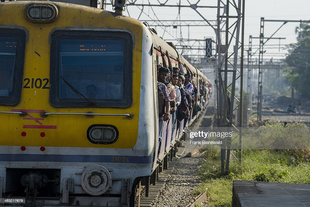 A crowded yellow train is arriving at Churchgate Railway Station, some people are dangerously travelling by leaning out of the doors.