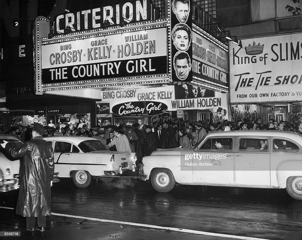 Crowds and taxi cabs gather outside the Criterion theatre in New York on for the opening of director George Seaton's film 'The Country Girl'. The marquee features headshots of the film's stars, Bing Crosby (top), Grace Kelly and William Holden.