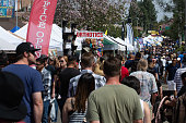 Throngs of festival-goers crowd each other as they move slowly past displays of food and goods.