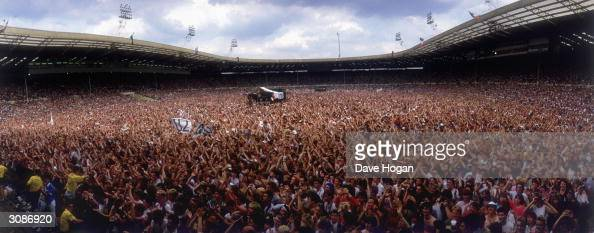 Crowds at the Live Aid concert at Wembley Stadium some waving U2 banners 13th July 1985