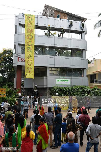 Crowds below watch as activists of GreenPeace rappell down their office building where they are head quartered to unfurl banners 'democracy' and...
