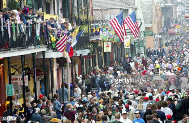 Crowds celebrate Mardi Gras along Bourbon Street February 24 2004 in New Orleans Louisiana Fat Tuesday celebrations draws a large crowd annually to...