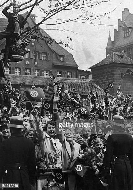 Crowds cheer and salute Nazi leader Adolf Hitler as he appears on the balcony of the Deutscher Hof Hotel Nuremberg during a visit to the city 5th...