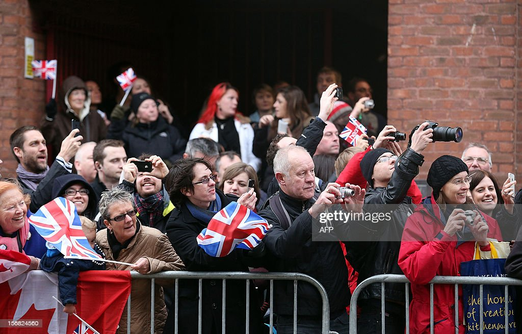 Crowds cheer and take pictures as Queen Elizabeth II, accompanied by Prince Philip, Duke of Edinburgh, arrive to tour the recently refurbished Bristol Old Vic Theatre on November 22, 2012 in Bristol, England.