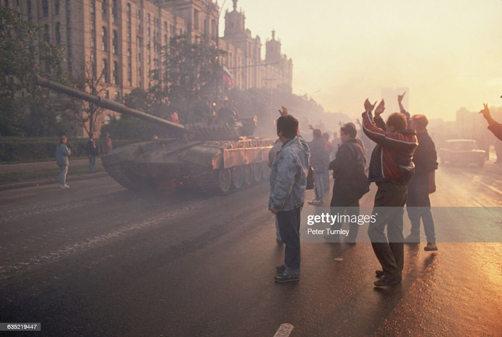 Crowds cheer as Russian soldiers pass by them in tanks following their defection to the side of Boris Yeltsin during the coup attempt by Soviet...