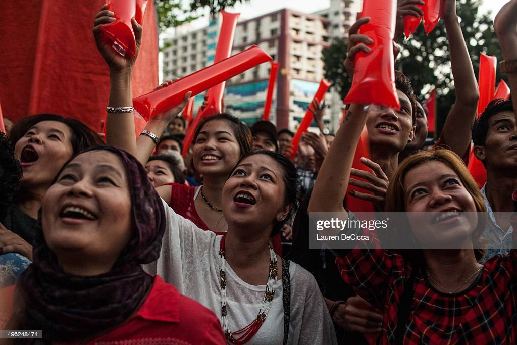Crowds cheer as they watch votes being counted at a National League for Democracy rally event at the end of voting day during Myanmar's first free...