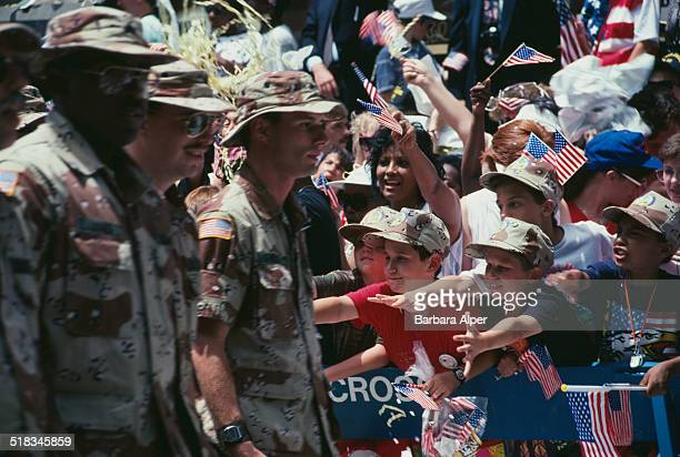 Crowds cheer at a ticker tape parade for US troops returning from the Gulf War New York City USA 11th June 1991