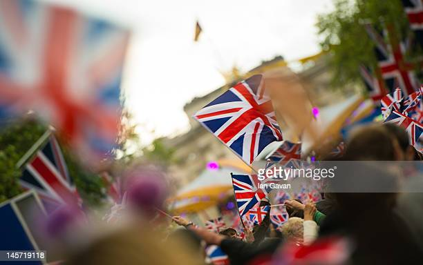Crowds gather and wave the Union Jack flag on The Mall during the Diamond Jubilee Buckingham Palace Concert on June 4 2012 in London England For only...