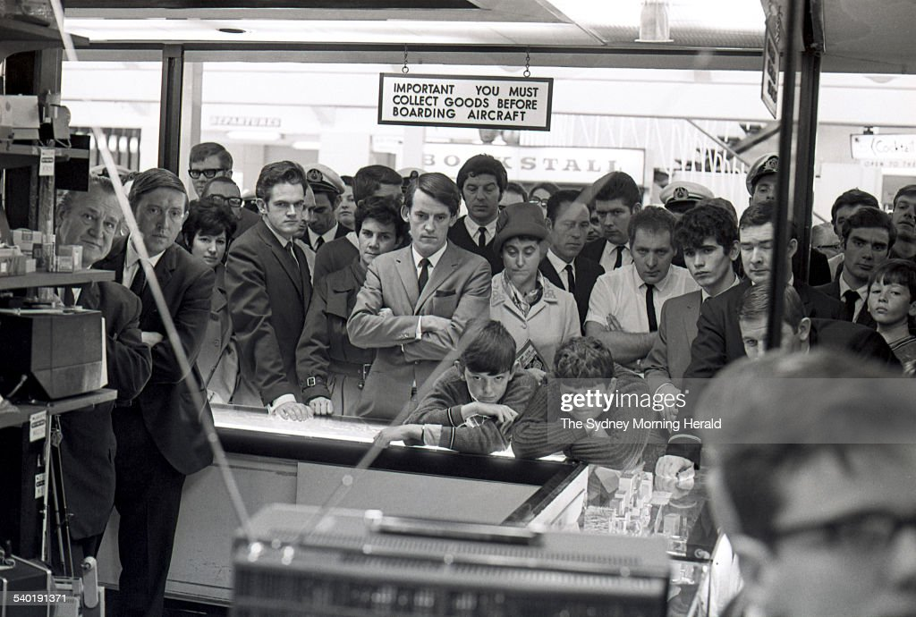 Crowds gather around a television set at Mascot Airport in Sydney to watch the broadcast of American astronaut Neil Armstrong becoming the first man...