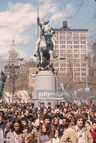 Crowds gather by a george washington statue in union square for earth