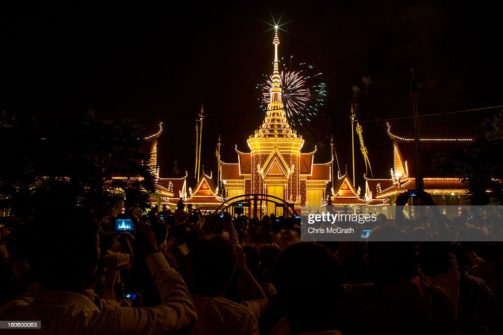 Crowds gather in the street to watch fireworks explode over the cremation site on the eve of the cremation of former King Norodom Sihanouk on February 3, 2013 in Phnom Penh, Cambodia. The former kings coffin was transported to the cremation site after being paraded through the capital in a lavish funeral procession. The cremation will take place on Monday the 4th of February, the funeral pyre will be lit by his wife and son King Norodom Sihamoni.