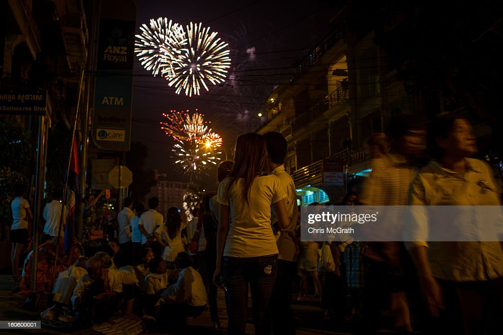 Crowds gather in the street to watch fireworks outside the cremation site on the eve of the cremation of former King Norodom Sihanouk on February 3, 2013 in Phnom Penh, Cambodia. The former kings coffin was transported to the cremation site after being paraded through the capital in a lavish funeral procession. The cremation will take place on Monday the 4th of February, the funeral pyre will be lit by his wife and son King Norodom Sihamoni.