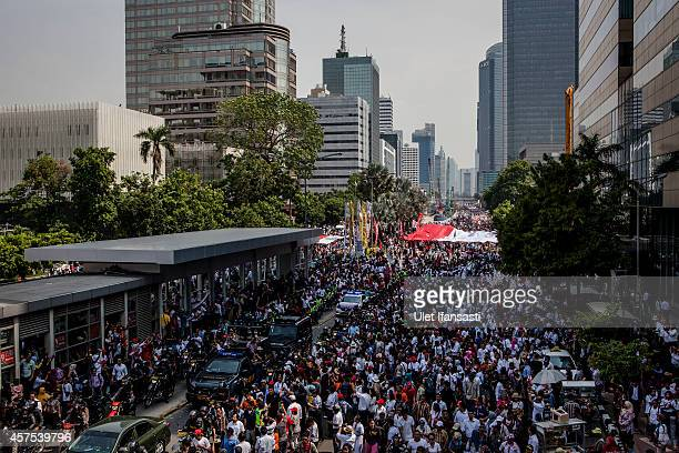 Crowds gather on the street as Indonesian President Joko Widodo and Vice President Jusuf Kalla journey to Presidential Palace by carriage during the...