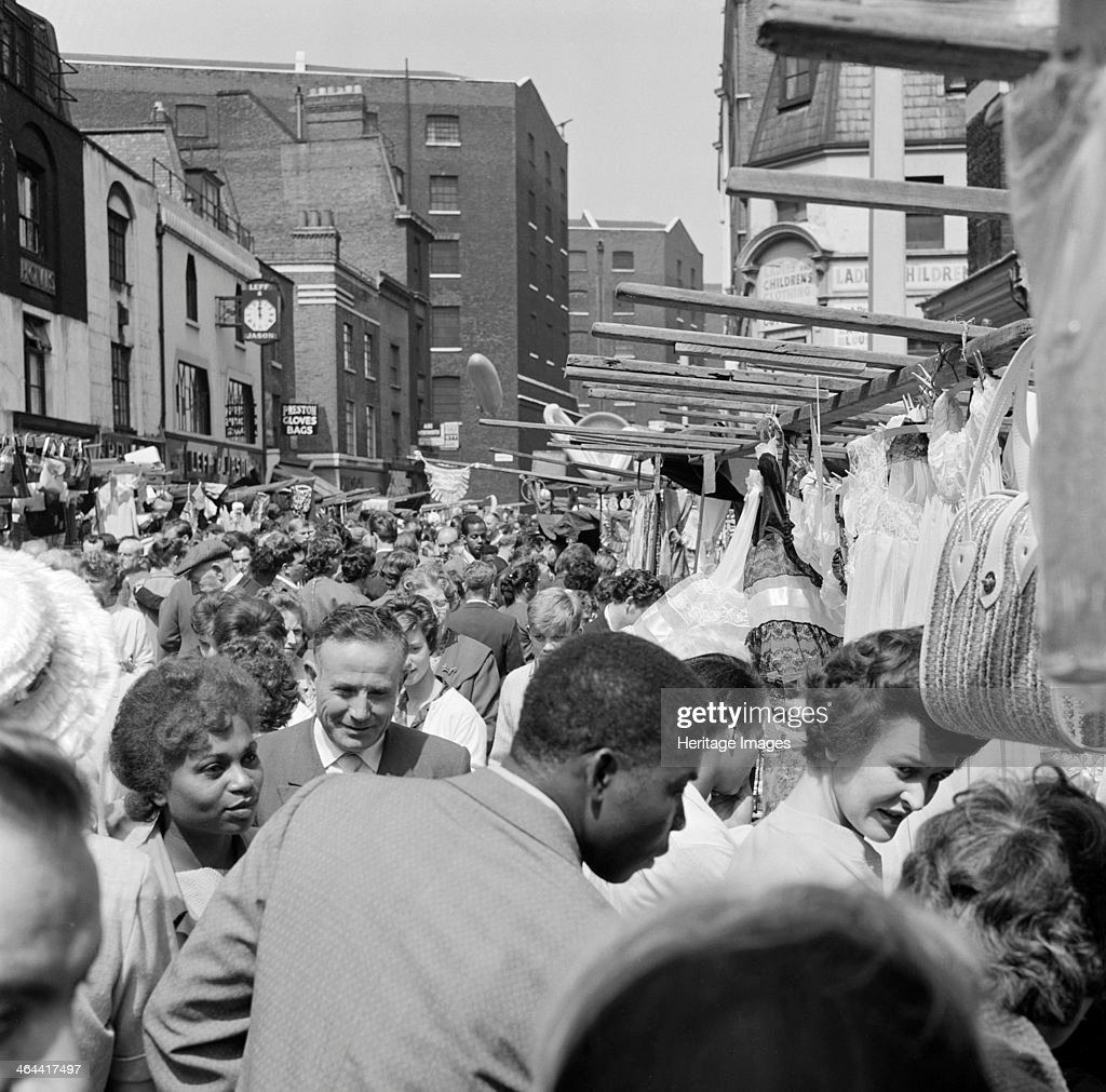 Crowds gathered around one of the stalls in Middlesex Street in the busy Petticoat Lane Market Whitechapel London c1946c1959