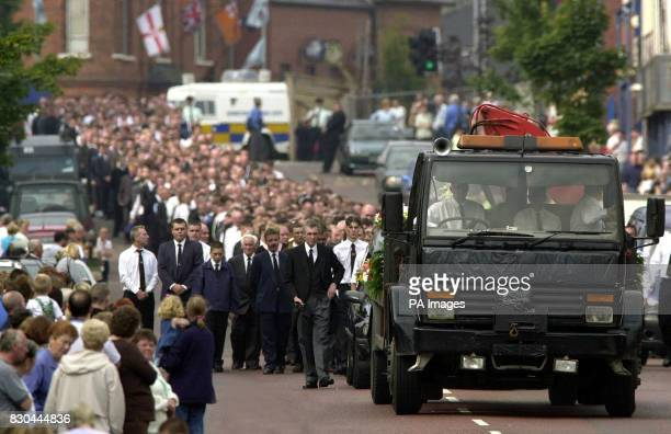 Crowds line the Shankill Road in Belfast as a flat bed lorry laden with floral tributes leads the funeral cortege of Samuel Rocket who was shot and...