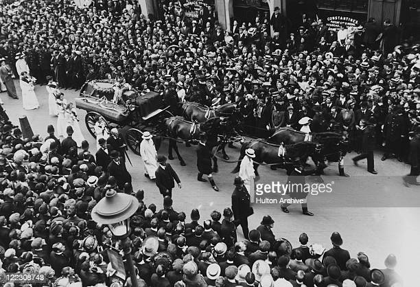 Crowds line the street as the funeral procession of English suffragette Emily Davison passes through a London street 14th June 1913 Davison died...