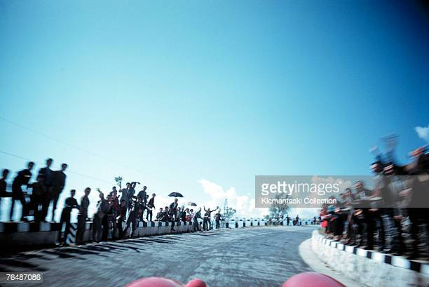 Crowds lining the road to wave and cheer as Peter Collins and Louis Klemantaski proceed across the mountains before Rome during the Mille Miglia May...