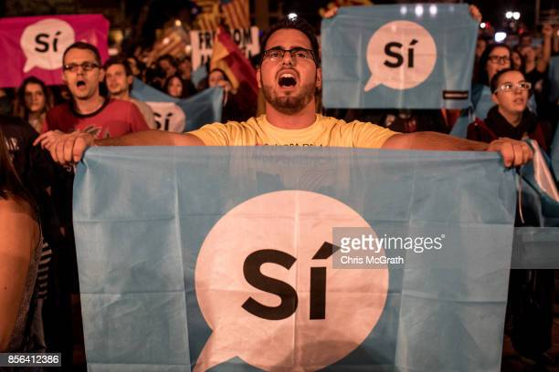 Crowds listen to Catalan President Carles Puigdemont speak via a televised press conference as they await the result of the Indepenence Referendum at...